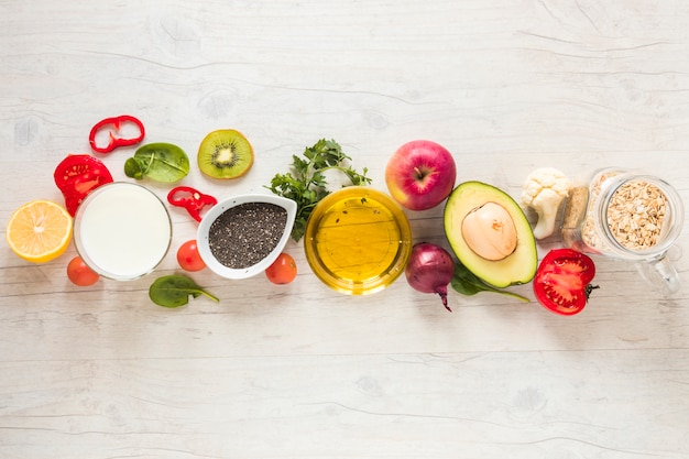 Oil; fruits; vegetables and oats arranged in a row on white textured background