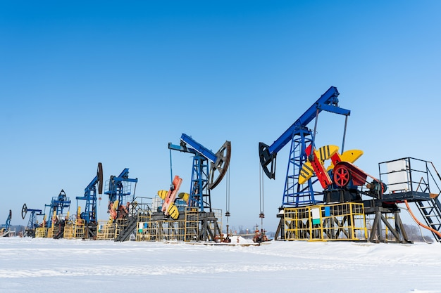 Oil and gas industry. working oil pump jack on a oil field at winter sunny day. oil production in siberia.