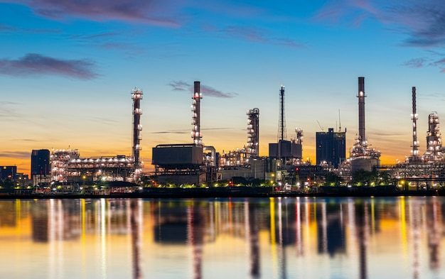 Oil and gas refinery industry plant with glitter lighting and sunrise in the morning