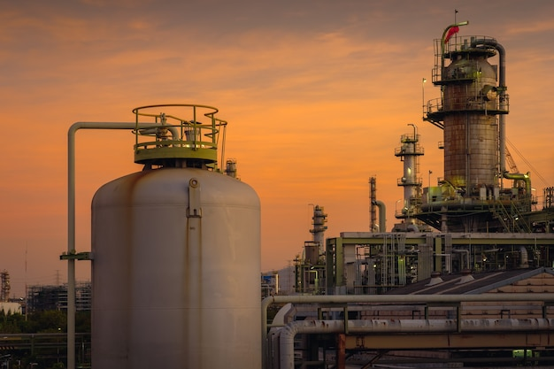 Oil and gas refinery pant on orange sky sunset background, petrochemical industry plant
