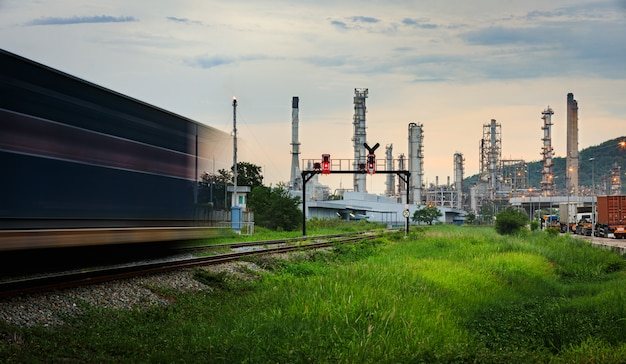 Oil and gas refinery plant storage area with train moving foreground and evening in thailand