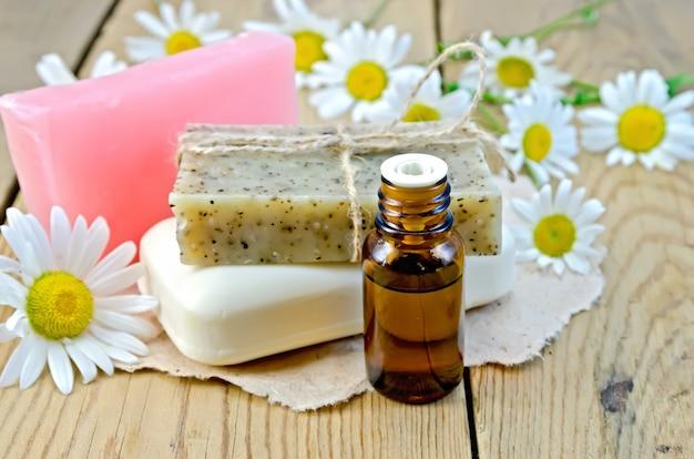 Масло в бутылке, домашнее мыло на листе бумаги, цветы ромашки на фоне деревянных досок