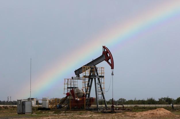 석유 산업. 석유 굴착 장치. 비와 무지개 후 오일 펌프입니다. 공간을 복사합니다.