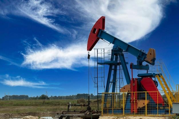 석유 산업. 석유 굴착 장치. 구름과 푸른 하늘 배경에 오일 펌프. 공간을 복사합니다.