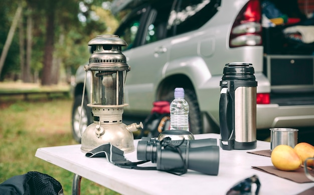 Oil lamp, thermos and binoculars over camping table in the forest with  offroad vehicle