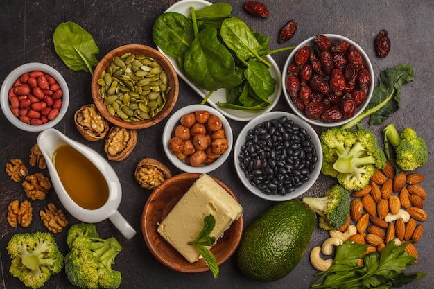 Oil, nuts, avocado, butter, healthy fats, rose hips, parsley, seeds, spinach. dark background, top view