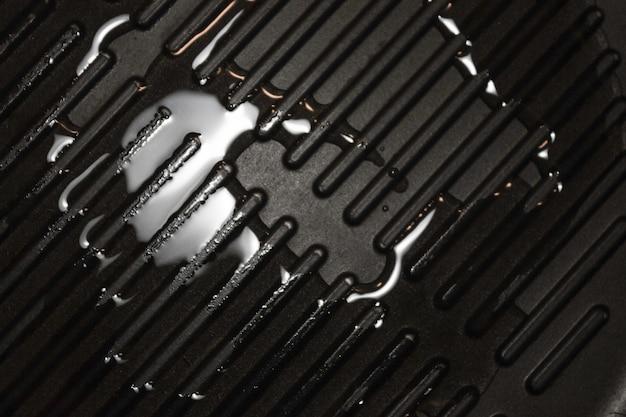 Масло на черной поверхности сковороды для гриля, copyspace. гриль сковорода макрос