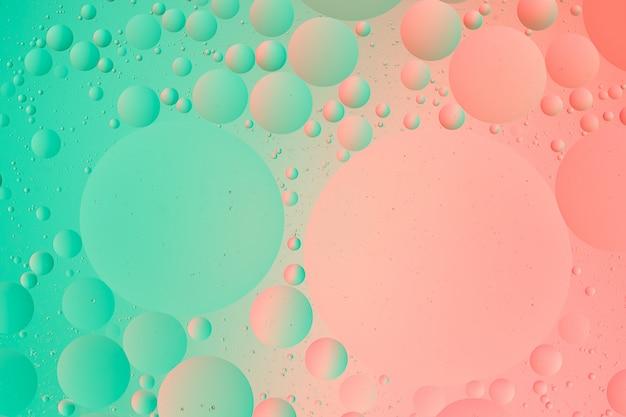 抽象的な緑とピンク色のグラデーションの背景の水マクロ写真の油