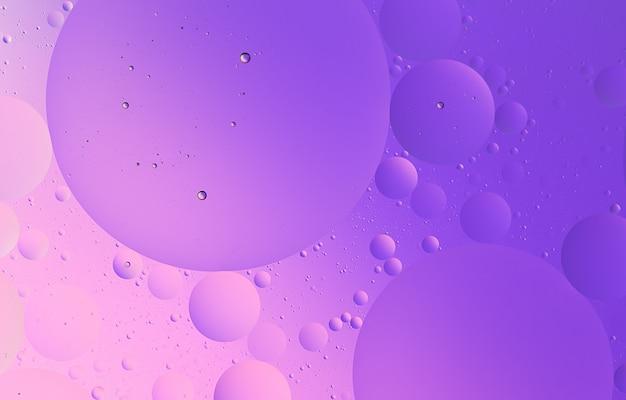 抽象的なピンクと紫の色のグラデーションの背景の水マクロ写真に油