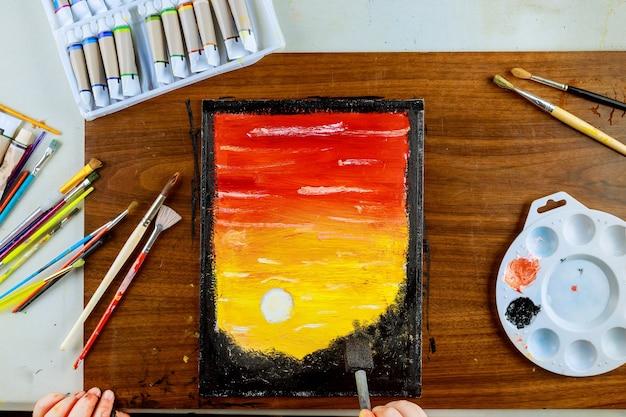 キャンバスに油絵。夕日の美しい風景。アートツール
