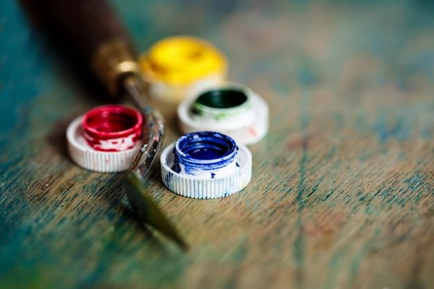 Масляные краски и шпатель над деревянной стеной