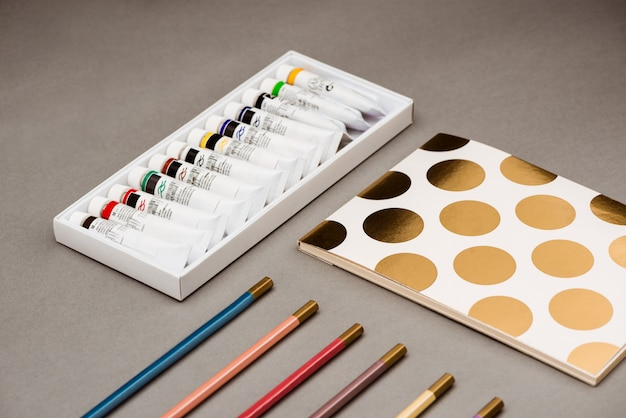 Масляные краски, карандаши и альбом на сером столе
