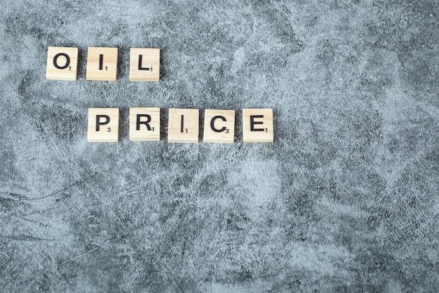 水平方向に木製のダイスに黒い文字で書く石油価格。高品質の写真