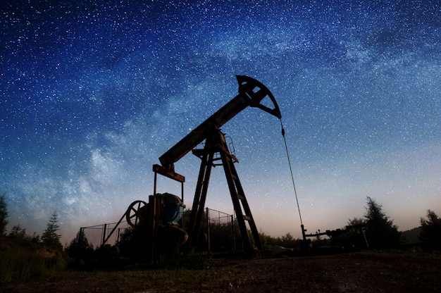 Oil pump jack pumping on the oil field in the night with starry sky galaxy. milky way