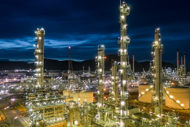 Нефтеперерабатывающий завод и нефтехимическая промышленность с резервуарами для хранения стальных трубопроводов в сумерках с высоты птичьего полета