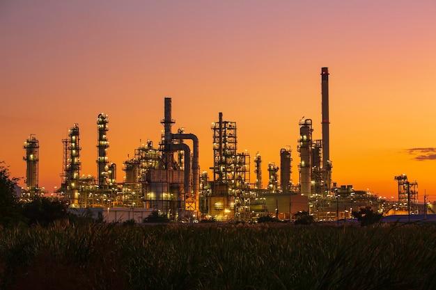Нефтеперерабатывающий завод и завод и башня колонны нефтехимической промышленности в нефтегазовой промышленности с облаком голубое небо на фоне восхода солнца