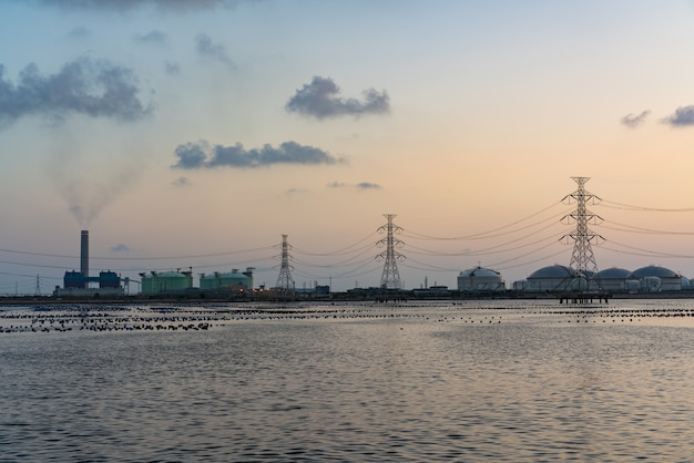 Oil refinery light river front reflection at twilight- industrial landscape background