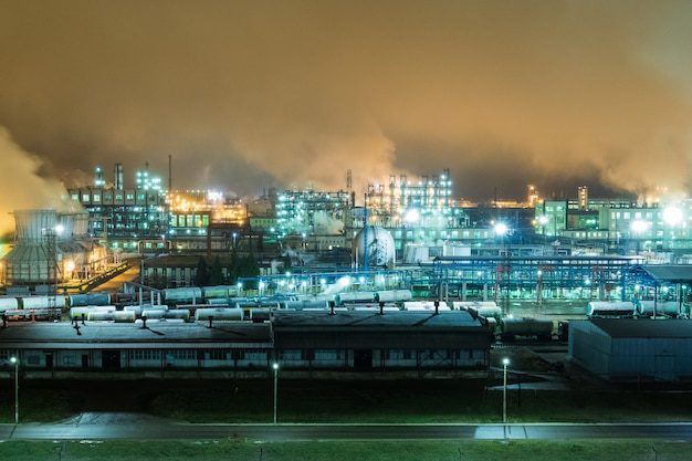 Oil refinery with pipes and distillation complexes at night