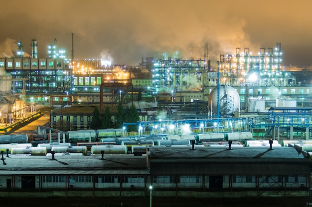 Oil refinery with pipes and distillation complexes at night.