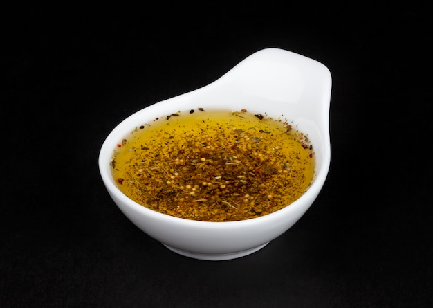 Oil salad dressing in white bowl isolated on black background