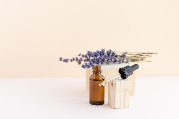 Oil, serum or collagen next to lavender flowers
