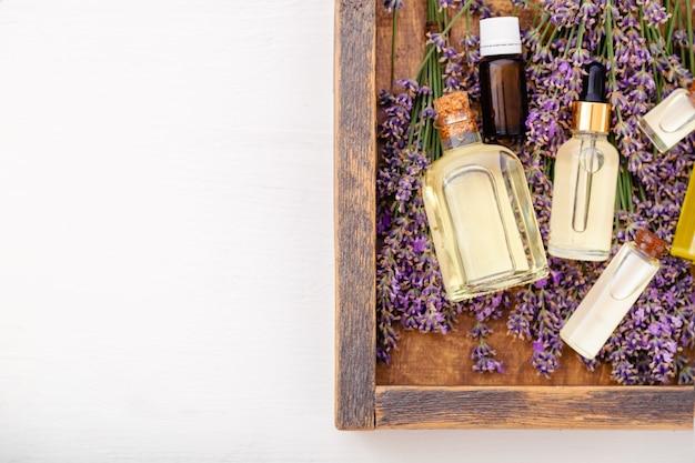 나무 상자에 있는 라벤더 꽃에 오일 세럼 오일. 라벤더 에센셜 오일, 세럼, 바디 버터, 마사지 오일, 리퀴드. 평면 위치 복사 공간입니다. 스킨케어 라벤더 화장품. 스파 미용 제품을 설정합니다.