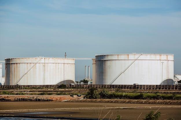 Резервуар для хранения нефти с нефтеперерабатывающим заводом трубопровод голубое небо.