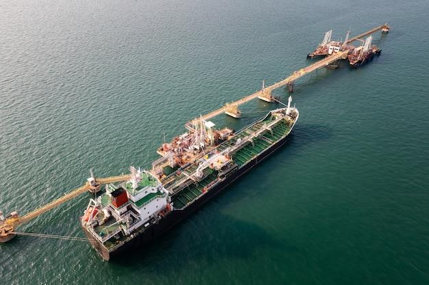 海上ビジネスの商業ドックでの石油とガソリンの積み下ろしの石油タンク船サービス輸送夕方の世界的な海上貨物ドローンからの空中上面図