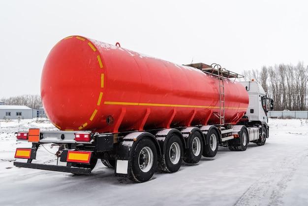 Автоцистерна с красным полуприцепом-цистерной снимок сделан в россии зимой в снегопаде.