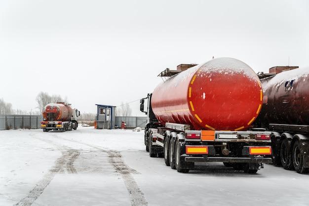 Semitrailertanker가 있는 유조선 트럭은 운송 기지의 영역에서 검문소를 통과합니다.