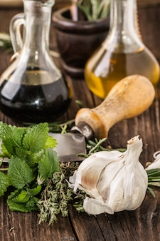 Oil and vinegar, gralic, knife and herbs