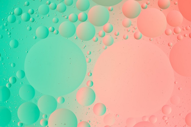 Oil on water macro photography of abstract green and pink color gradient background