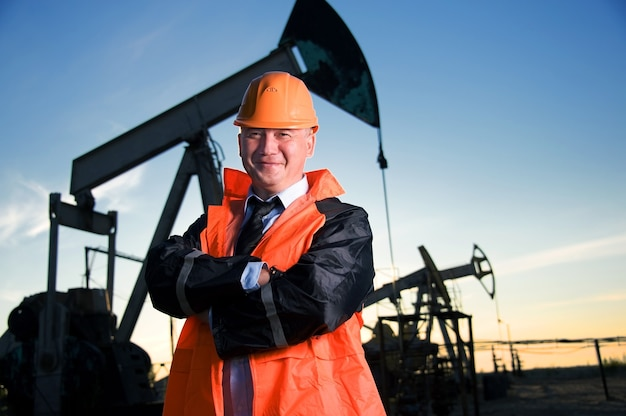 Нефтяник в оранжевой форме и шлеме на фоне домкрата насоса и закатного неба.