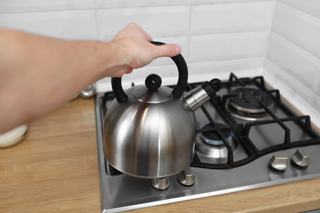 台所で金属のやかんを持っている男の手。やかんはお湯を使って、お茶、コーヒー、粉ミルクなどの飲み物をoilでます。