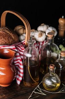 Масла и специи возле кувшина и продуктов питания