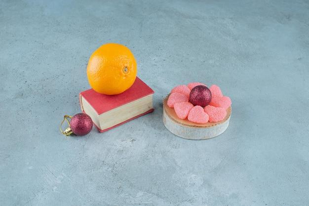 Arancia su un libro, marmellate su un pezzo di legno e due palline decorative su marmo.