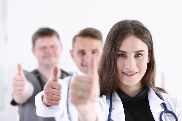 医師のグループは、肖像画を親指でokまたは承認のサインを表示します。高レベルのサービス、最高の治療911健康的なライフスタイルに満足する患者の治療士相談物理的な概念