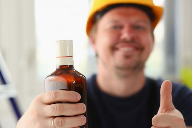 黄色いヘルメットの酒に酔った労働者の腕は、okジェスチャーを表示するか、クローズアップを親指でサインを確認します。手動の仕事場diyのインスピレーションフィックスショップハード帽子産業教育職業キャリア
