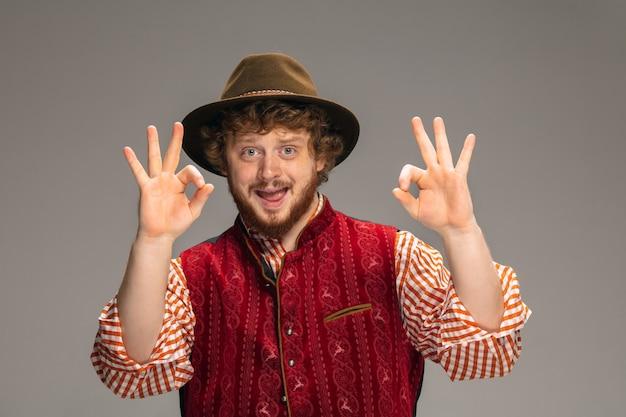 Okジェスチャー。灰色のスタジオの背景に分離されたジェスチャーで伝統的なオーストリアまたはバイエルンの衣装に身を包んだ幸せな笑顔の男。コピースペース。お祝い、オクトーバーフェスト、お祭り、伝統のコンセプト。