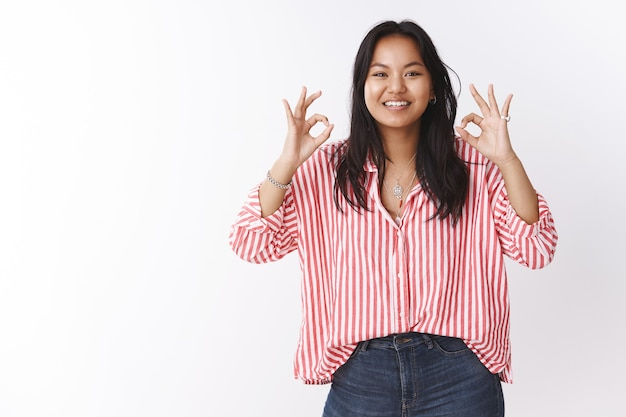 Ok got it, count on me. portrait of active and energized confident young female coworker assuring she knows what do showing okay gesture to relax friend, smiling, doing excellent job over white wall