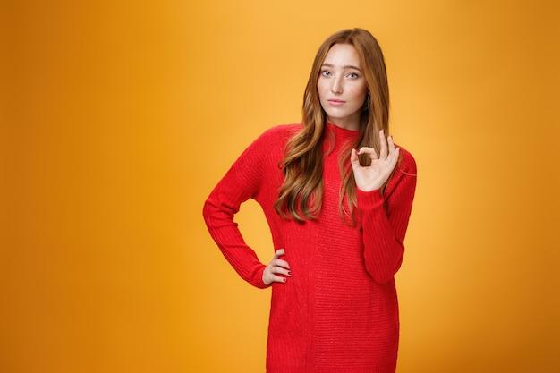 Ok ho capito. ritratto di imprenditrice fiduciosa e prepotente con i capelli rossi che mostra un gesto ok che dà una risposta positiva, conferma qualcosa, soddisfatta di uno sforzo eccellente e perfetto