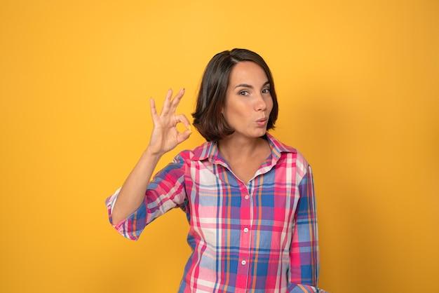 Ок или ок знак с улыбкой одной поднятой руки красивая женщина, одетая в клетчатую рубашку