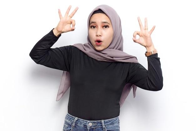 젊은 아름다운 이슬람 아시아 여성의 ok 사인 제스처는 베일 히잡과 검은 셔츠를 입습니다.