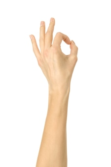 Ok sign. woman hand with french manicure gesturing isolated on white wall. part of series