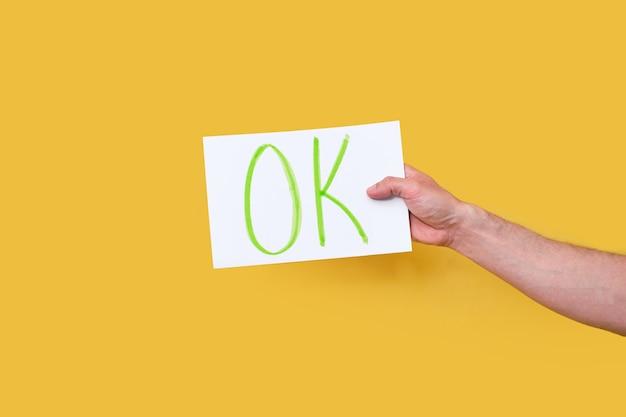 黄色の孤立した背景の上の白い紙の段ボールに手書きのok単語