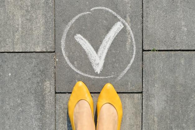 Галочка ok знак на сером тротуаре с женскими ногами, вид сверху