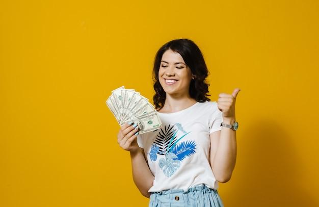 お金の紙幣の束を押しながら黄色の壁で分離された[ok]ジェスチャーを示す笑みを浮かべて少女の画像