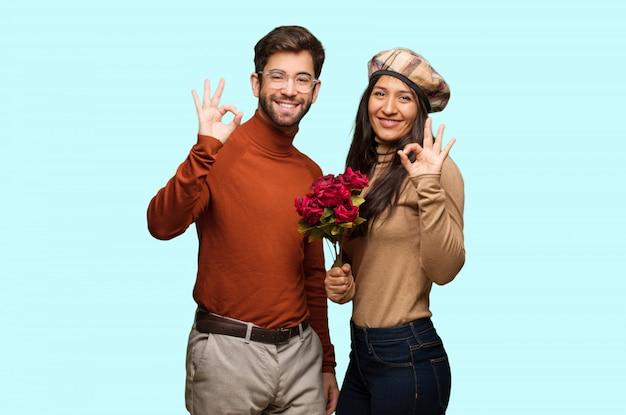 陽気で自信を持ってokのジェスチャーをやっているバレンタインデーの若いカップル