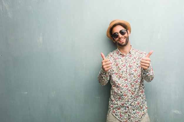 陽気で興奮して、笑みを浮かべて、彼女の親指を立てる、成功と承認、okのジェスチャーの概念のカラフルなシャツを着ている若い旅行者男性