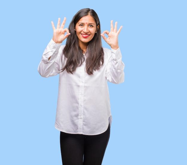 陽気で自信を持ってokのジェスチャー、興奮して叫んで、承認と成功の概念をやっている若いインド人女性の肖像画